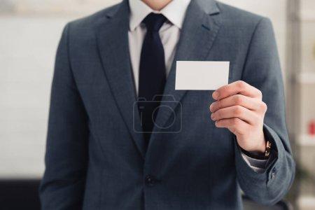 Photo pour Vue recadrée de l'homme d'affaires dans l'usure formelle retenant la carte de visite blanche - image libre de droit