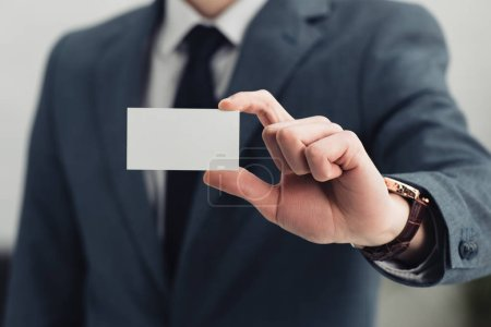 cropped view of businessman in formal wear showing empty business card at camera
