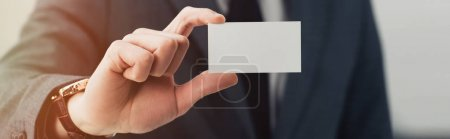 Photo for Partial view of businessman in formal wear showing empty business card at camera, panoramic shot - Royalty Free Image