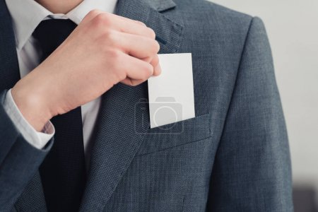 cropped view of businessman in suit holding blank business card