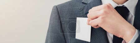 Photo for Partial view of businessman in suit holding blank business card, panoramic shot - Royalty Free Image