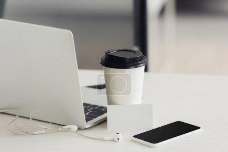 Foto de Portátil, teléfono inteligente con pantalla en blanco, taza de papel y tarjeta de visita en blanco en la mesa de la oficina - Imagen libre de derechos