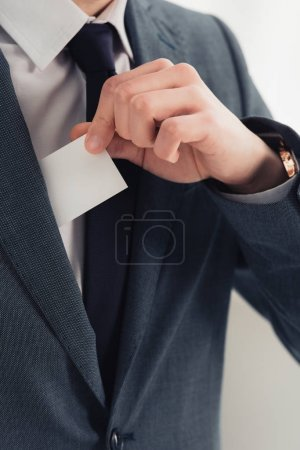 Photo for Cropped view of businessman in suit holding white empty business card - Royalty Free Image