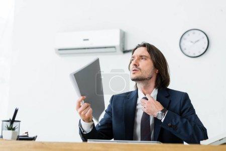 Photo pour Homme d'affaires assis au bureau avec le dossier à la main, détournant les yeux et souffrant de chaleur - image libre de droit