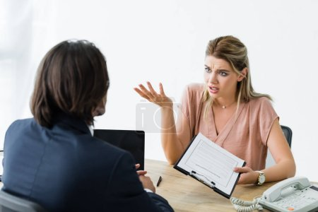 Photo for Confused woman talking with businessman while holding contract in hand - Royalty Free Image
