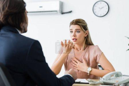 enfoque selectivo de la mujer preocupada gesto y mirando a los hombres de negocios