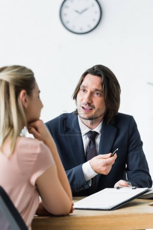 selective focus of businessman talking with client about contract