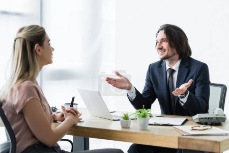 selective focus of cheerful businessman talking with client in office