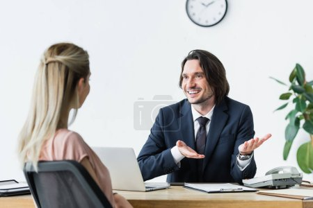 Photo pour Foyer sélectif de l'homme d'affaires joyeux parler avec le client au bureau - image libre de droit