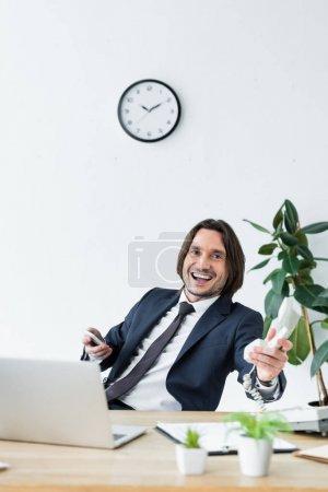 Photo pour Homme d'affaires heureux retenant le casque et le smartphone dans des mains, s'asseyant derrière la table et regardant l'appareil-photo - image libre de droit