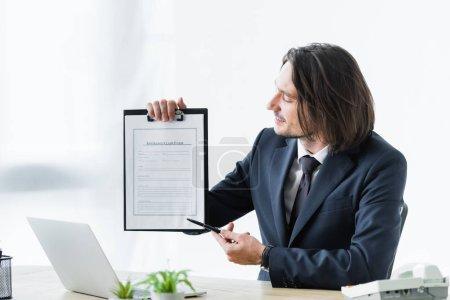 Photo pour Homme d'affaires pointant avec la plume sur le formulaire de réclamation d'assurance - image libre de droit