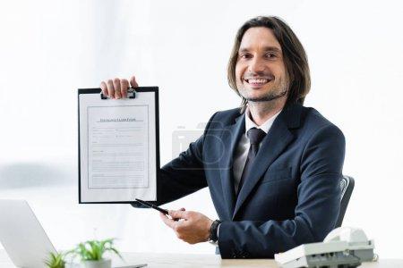 Photo pour Homme d'affaires heureux retenant le formulaire de réclamation d'assurance dans la main et regardant l'appareil-photo - image libre de droit
