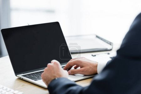 Photo for Cropped view of businessman working with laptop and sitting at table - Royalty Free Image