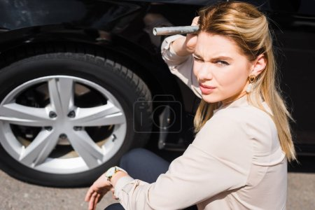businesswoman with tool in hand sitting near broken auto, car insurance concept