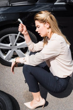 Photo for Upset businesswoman with tool in hand sitting near broken auto, car insurance concept - Royalty Free Image