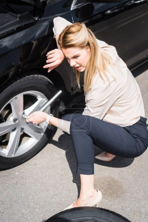 Photo for Tired businesswoman with tool in hand sitting near broken auto, car insurance concept - Royalty Free Image