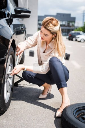 Photo for Businesswoman fixing wheel on broken auto, car insurance concept - Royalty Free Image