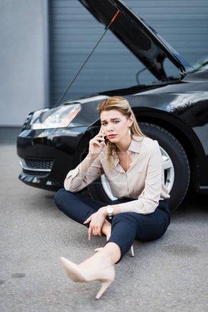 Photo pour Femme d'affaires bouleversé parler sur smartphone près de l'automobile cassée, concept d'assurance automobile - image libre de droit