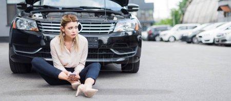Photo pour Tir panoramique de femme d'affaires bouleversée assis près de l'auto cassée avec smartphone dans les mains, concept d'assurance automobile - image libre de droit