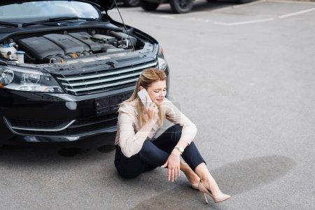 sad businesswoman talking on smartphone while sitting near broken auto, car insurance concept