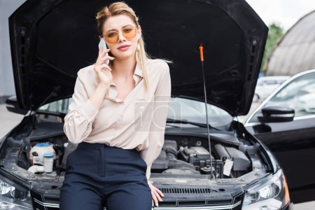 Photo for Businesswoman talking on smartphone near broken auto with open trunk, car insurance concept - Royalty Free Image