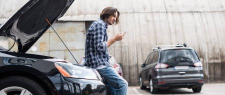 Photo for Panoramic shot of man with smartphone standing near broken auto with open trunk, car insurance concept - Royalty Free Image