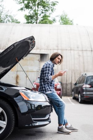 Photo for Handsome man with smartphone standing near broken auto with open trunk, car insurance concept - Royalty Free Image
