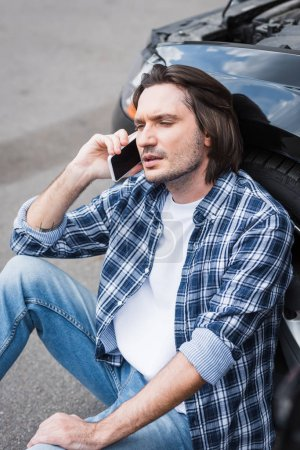 Photo for Tired man sitting near broken auto and talking on smartphone, car insurance concept - Royalty Free Image