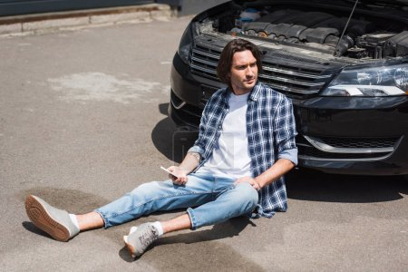 Photo for Handsome man holding smartphone in hand, looking away and sitting near broken auto with open trunk, car insurance concept - Royalty Free Image