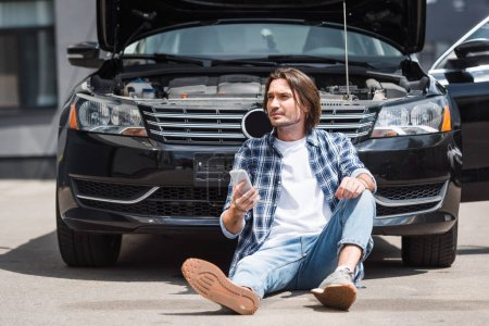 Photo for Man in casual clothes holding smartphone in hand, looking away and sitting near broken auto with open trunk, car insurance concept - Royalty Free Image