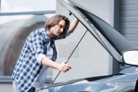 Photo for Handsome man in casual clothes standing near broken auto with open trunk, car insurance concept - Royalty Free Image