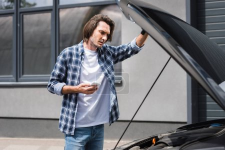 Photo for Handsome man holding smartphone in hand and standing near broken auto with open trunk, car insurance concept - Royalty Free Image