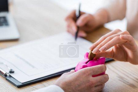 Photo pour Vue recadrée de la femme mettant pièce dans tirelire et document de signature - image libre de droit