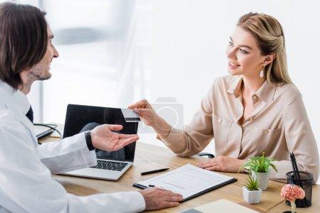 Photo pour Patient beau et heureux donnant la carte de crédit au docteur - image libre de droit