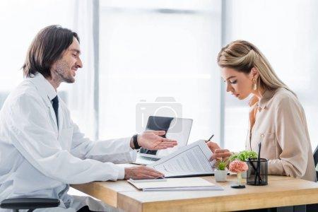 Photo pour Femme signant le formulaire de demande d'assurance pendant le rendez-vous avec un médecin en clinique - image libre de droit