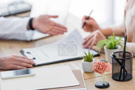 Photo for Cropped view of doctor with patient signing insurance claim form - Royalty Free Image
