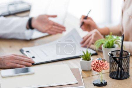 Photo pour Vue recadrée du médecin avec patient signant le formulaire de demande d'assurance - image libre de droit