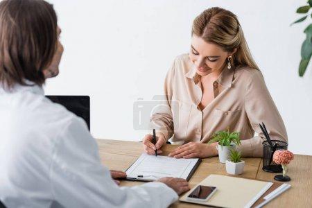 Photo pour Belle femme signant formulaire de réclamation d'assurance près du médecin en clinique - image libre de droit