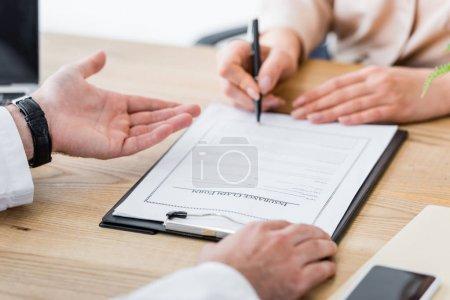 Photo pour Vue recadrée de la femme signant le formulaire de demande d'assurance près du médecin en clinique - image libre de droit