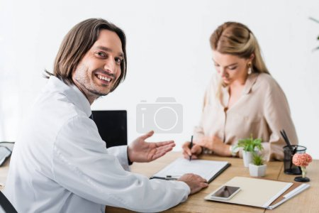Photo for Selective focus of happy doctor looking at camera while patient signing document - Royalty Free Image