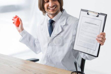 Photo pour Heureux médecin tenant coeur rouge et formulaire de demande d'assurance dans les mains - image libre de droit