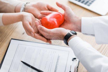 Photo pour Vue recadrée du médecin et du patient tenant le cœur rouge dans les mains, concept d'assurance médicale - image libre de droit