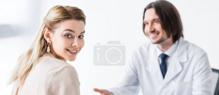 Photo for Panoramic shot of beautiful patient visiting doctor and looking at camera - Royalty Free Image
