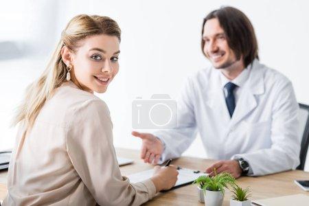 Photo pour Médecin heureux de visite de patient, regardant l'appareil-photo et document de signature - image libre de droit