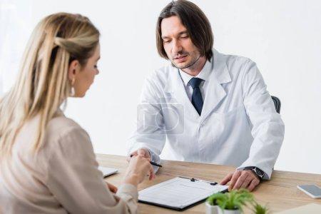 Photo pour Patient assis avec le médecin derrière une table en bois et document de signature - image libre de droit