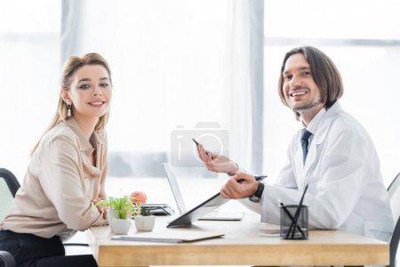 Photo pour Patient et docteur s'asseyant derrière la table en bois et regardant l'appareil-photo - image libre de droit