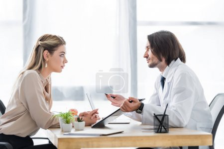 Photo for Side view of patient looking at doctor with document in hand - Royalty Free Image