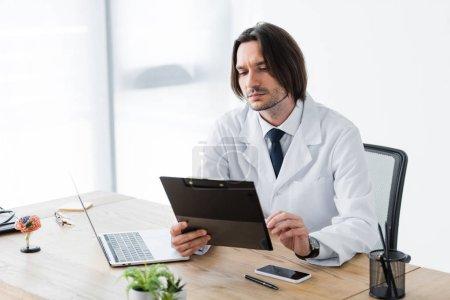 Photo pour Beau médecin avec presse-papiers dans la main assis dans le bureau au bureau - image libre de droit