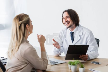 selective focus of happy doctor with clipboard in hand talking with patient