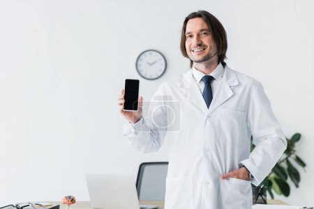 Photo pour Cheerful doctor in white coat looking at camera and holding smartphone in hand - image libre de droit